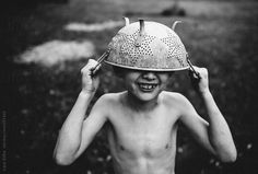 Boy plays outside in his backyard wearing a colander as a hat by Cara Slifka #stocksy #realstock