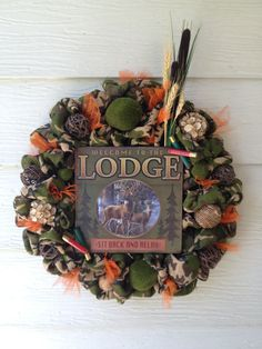 "Camouflage burlap ""Hunter"" wreath, embellished with deco balls, moss covered ""rocks"", hazard orange tulle, shot gun shells and cattails and wheat."