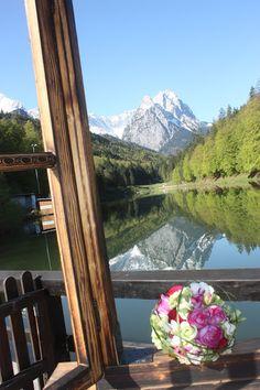 Hochzeit in den Bergen in Bayern am See - Brautstrauß im Panoramafenster am…