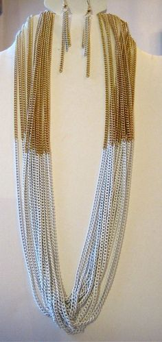 Byras half dipped white and gold multi chain necklace set will have you draped in sexy chains. The multi layered necklace is a two-tone of white and gold, as are the tassel earrings.Brass Base MetalGold Tone Finish, white Tone Finish16 Inches Long$20.00 set https://www.facebook.com/DJewelryDesign
