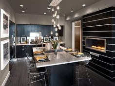 A wide granite kitchen island serves as both an island and dining area with a custom built black and white fireplace nearby adding to the ambiance.