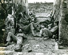 """Okinawa, 29 May 1945  The caption on this photograph reads """"Battle Weary-Marines of a Sixth Division mortar crew snatch forty winks after a hard night of fighting for the capital city of Naha."""""""