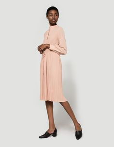 Vintage-inspired dress from Farrow in Rose. High crew neckline. Partial button placket. Long sleeves with single button barrel cuff. Straight back yoke. Micro-pleating at bodice. Cinches at waistline with drawcord adjustment. Unlined.  • Crepe • 97% po