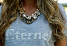 Love the way she layers on glam statement necklaces with a casual tee. Style inspiration via A Fashion Love Affair.