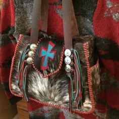 A custom cowhide Bonnie Bag. This customer requested a red and turquoise suede cross and fringe. Suede lined side pockets top it all off. gowestdesigns.us