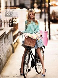 Girl on a bike with flowers & hatboxes.