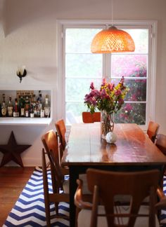 Informal dining area.  Efficient use of space.  Farm table with mid-century modern chairs.  Mini-bar in built-in desk.