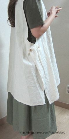 Lightweight cotton pinafore apron. I really like pinafore aprons, but if I had been the one taking the picture, I would have made her put down her phone first.
