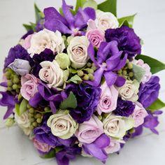 A bouquet of purple lisianthus, mushroom 'Creme de Menthe' roses, mauve 'Pacific Blue' roses, purple vanda orchids, and berzillea berry.