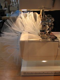Once the tulle/netting is ironed flat, it is run through the sewing machineusing a special gathering foot. After this, another gathering thread iszig-zagged on top of this gathering so that each piece can be gathered evenmore tightly to fit the appropriate space on the basque/panty.