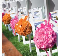 The Ceremony Decor: Flower balls in pink and orange hung from the chairs lining the rose petal–strewn aisle