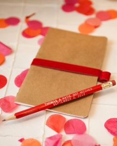 """Details, details, details! This couple gave out mini Moleskine notebooks embossed with the newlyweds' logo on the front cover as wedding favors. The personalized pencils read """"Thomas and Katie Got Hitched, September 2, 2012"""" in white lettering and were cut down to 5 inches to line up perfectly with the height of the notebooks."""