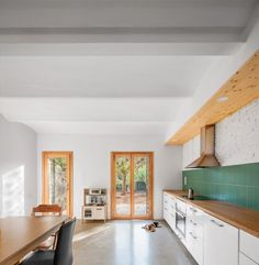 At the back of the home is a kitchen-dining space, where a simple run of countertops with a green tile splash back sit opposite a large central table, alongside doors leading out to the garden. Patio Interior, Cladding, Minimalism, Two By Two, Indoor, Contemporary, Gallery, House, Kitchens