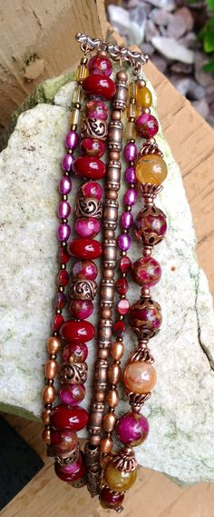 Bracelet - like the variation in size/color/shape of strands. To try similar in other than pink/red