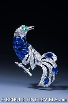 CARTIER - An Impressive Sapphire, Emerald and Diamond Bird Brooch, designed as a bird sitting on a baguette cut diamond branch. The brilliant cut diamond head with Emerald eye and baguette cut Diamond feathers, the body set with oval Sapphires highlighted with blue enamel cabochons. The brilliant cut Diamond openwork wings and tail set with three oval Sapphires. Double prong brooch fitting with safety clasp. Mounted in Platinum and 18 karat Gold.