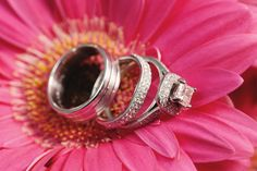 Creative wedding ring photo wedding rings with bright pink gerber daisy flower. Image by Kokoro Photography on MarryMeMetro.com