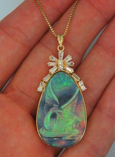 Custom Made Natural Opal Pendant.  Very High Quality Australian Black Opal with lots of rainbow colors. Hand carved of a swan. Carving is in perfect condition. Very rare opal piece. This is completely natural Opal, no treatment.  Accented by diamonds 1.60 total carat weight.