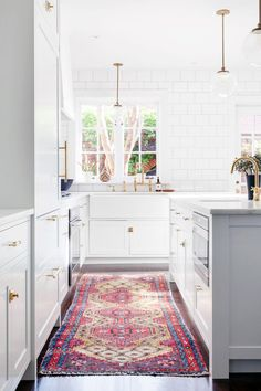 Favorite Kitchens of 2015 - How amazing is this vintage persian colorful rug in this all white kitchen. Holy pop of color!