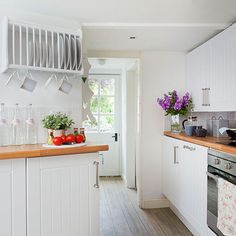 White kitchen with panelled white cabinetry, wood worktops and white plate rack