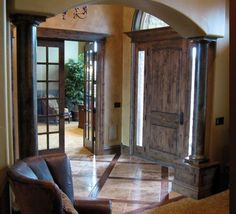 Tuscan style interior. This entryway is so warm and cozy with the rich wood door. I love all of the natural light too. Solid wood front door with side lights