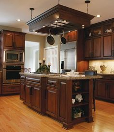 LOVE this home with dark stained cupboards and light hardwood floors and a very classy pot rack hanging above the island.