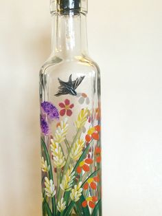 Hand painted wild flowers in vibrant shades purple, yellow, orange, red, blue and green on glass bottle, accented by birds. Many people use these