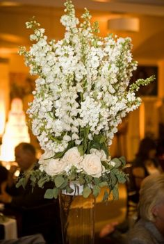 Tall centerpiece loaded with white delphinium and the base of creamy roses and seeded eucalyptus