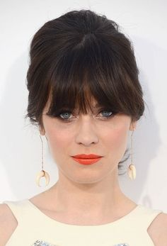 Zooey Deschanel brings back the 60's mod look with orange lips and an updo.