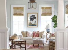 Beautiful living room by Holly Mathis and photographed by Becki Griffin. I love how fresh this space looks. It's updated and timeless all at the same time. Really pretty living room with bamboo Roman Shades, white slip-covered sofa, layered rugs, a beauti