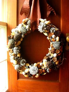 Rustic and silvered elements combine in this elegant holiday wreath. A grapevine base is encrusted with seed pods, pine cones, dried fruits and nuts, and echinacea heads. Silvered cones and seeds contrast the rusticity of the natural elements to complete this stunning wreath. It measures approximately 22 inches in diameter and is suspended by a satin chocolate ribbon, subtly edged in glitter. Although my materials are treated with a preservative, dried flowers are inevitably affected by…