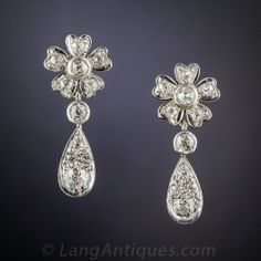 From the first decade of the last century, delightful original Edwardian diamond drops, hand-fabricated in platinum over 18K gold, with a diamond dangle sparkling below a diamond-set flower. Classics. 7/8 inch long, just shy of 1 carat.
