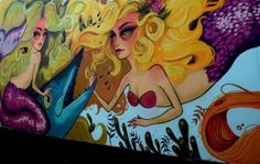 Mermaids stare at people as they walk past by on the side of a building along Harrison Street in downtown Hollywood. The mural of mermaids w...