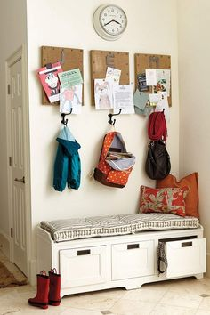 banc d'entrée blanc avec rangements, matelas et coussins et des patères