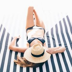 Dreaming of warmer weather.  Simple black bathing suit and straw hat to sit by the sea. #vacation #summer #fashion