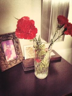 Another vintage frame houses a reprint of a Ravi Verma painting - flanked by red carnations!