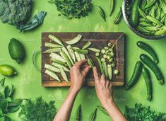 #Flat-lay of healthy green vegan cooking ingredients  Healthy green vegan cooking ingredients. Flay-lay of female hands cutting green vegetables and greens over green background top view. Clean eating vegetarian detox dieting food concept