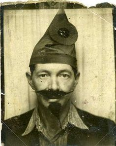 Vintage photo booth picture, man in Robin Hood (?) hat with fake mustache and beard.