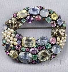"""Arts  Crafts Gem-set Brooch, Attributed to Dorrie Nossiter, designed as a wreath, prong-set with various cushion and circular-cut colored sapphires, emeralds, pink tourmaline, amethyst, and star sapphires, with seed pearl grape clusters, blackened silver mount, lg. 2 1/8 x 2 in., marked """"ENGLAND""""."""