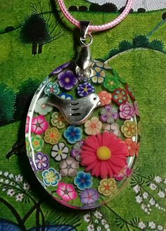 Resin pendant with flowers and bird.