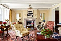 In the living room, a Franz Kline painting overlooks a Larrea Studio cocktail table with gilt-wood details; the mantel is by Jamb, and the Venetian-plaster walls were finished by Mark Uriu. The custom-made tufted armchair in the foreground is clad in an Old World Weavers silk, and the 18th-century English chair opposite is in a Schumacher print.