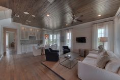 Warmth exudes from this Chi-Mar living room thanks to the wooden ceilings and floors.  http://chimarconstruction.com/