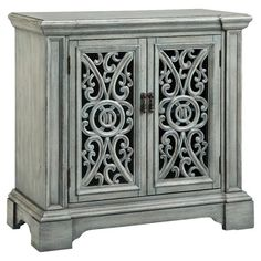 Showcasing carved scroll door fronts and a hand-painted verdigris finish, this artful cabinet is a stylish addition to your living room or parlor. ...