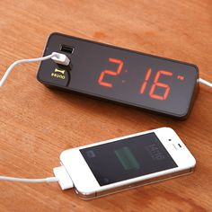 An electronic LED clock with a USB power supply port. Tired of always having to find a separate outlet for your phone or camera? Suitable for the desk or your bedside table, the sleek, modern alarm clock incorporates 2 USB outlets that are perfect for charging an iPhone or ay other device supported by a USB charge.  Exclusive AC adapter included, can also run on 3 AA batteries (not included)