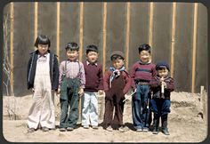 A group of children line up for a photo in front of a barrack wall. Billy Manbo is on the far right.