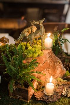 Woodland-themed wedding table centerpiece, featuring vintage, brass deer figurines amidst ferns and moss-covered wood stumps.  Union Hill Inn Wedding - March 2016
