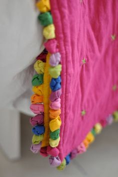 The the idea of colored knots along the edge of a quilt.  It reminds me of pom pom fringe.  Wish there was a tutorial on this post but I believe the item was store bought.  Great inspiration.