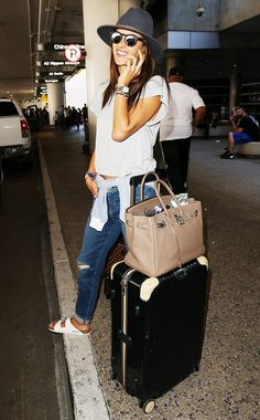 Alessandra Ambrosio wears a gray t-shirt, distressed jeans, Birkenstocks, mirrored sunglasses, a fedora, and an Hermes Birkin bag