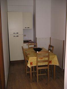 Angolo pranzo, con tavolo e frigorifero