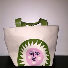Kate Spade Sun Face Beach Bag This is a used Kate Spade Sun Face beach bag. Canvas bag light tan with a green, pink, and black colored sun face. The leather handles are a lime green that match the green on handles. The bag has a leather tie to tie at the top. There are some light marks in edge of bottom of bag and on canvas. There are some scratches on the leather. I will pour up another listing with more pics. Have never tried to spot clean canvas though I'm sure it could be. kate spade…
