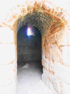 Menasalbas. Despoblado de Jumela. Entrada a torre de la Iglesia de la Asunción de Nuestra Señora. Se pueden apreciar la presencia de graffitis modernos en la bóveda del arco de entrada